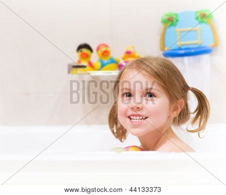 Cute happy baby girl taking bath with foam and toys, child's hygiene, healthy lifestyle, carefree childhood concept