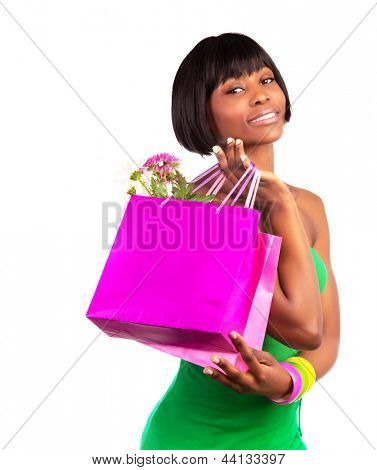 Attractive african female with pink shopping bag isolated on white background, paper bag with flowers, luxury lifestyle