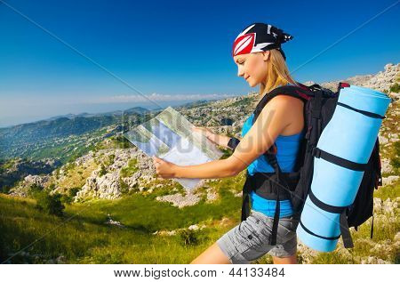Young sporty woman standing on the peak on mountain watching on map, extreme adventure, happiness and freedom concept