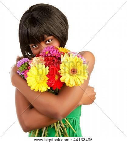 Beautiful african woman holding in hands and smelling big colorful bouquet of flowers, isolated on white background