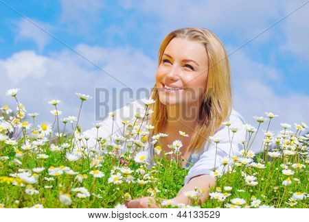Pretty woman lying down on daisy field, cute female enjoying little white spring time flowers, having fun outdoors