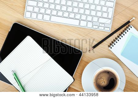 Office supplies, gadgets and coffee cup on wooden table