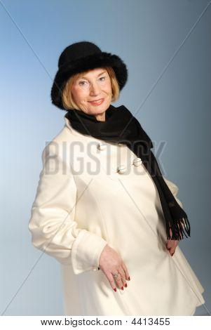 attraktive ältere Frau in Wintermantel & Hut