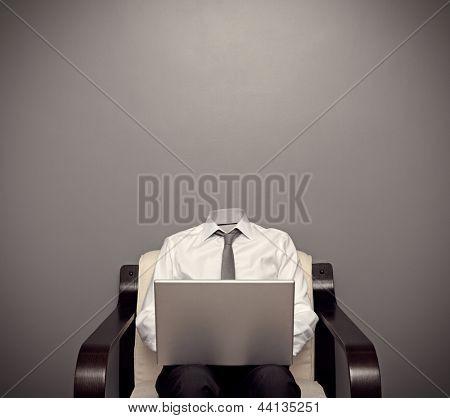 homem invisível no desgaste formal sentado na cadeira e trabalhar com o laptop contra fundo cinza
