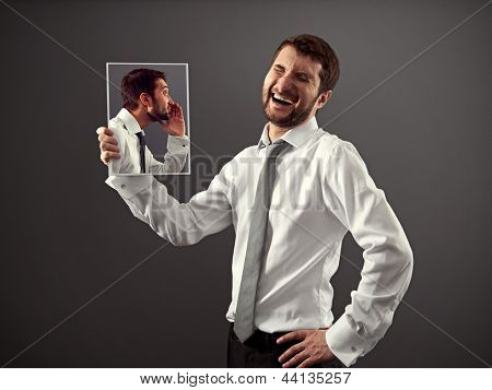 man in formal wear is laughing at a joke