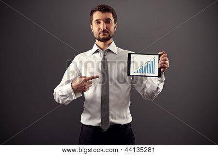 empresario serio con tablet pc y apuntando a la tabla de crecimiento