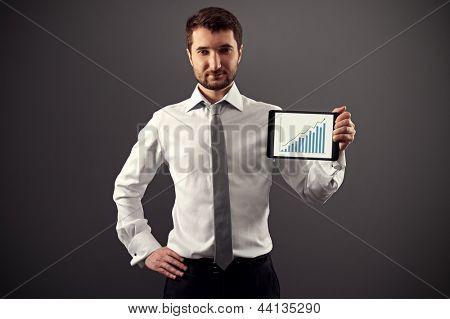 seguro de hombre en ropa formal que muestra la tabla de crecimiento sobre fondo oscuro