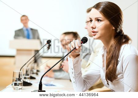 Business woman speaks into a microphone