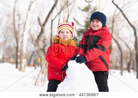 Boy and girl playing with snow in winter park