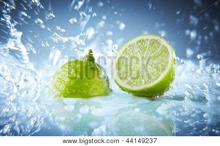 Water splash on lime isolated on blue