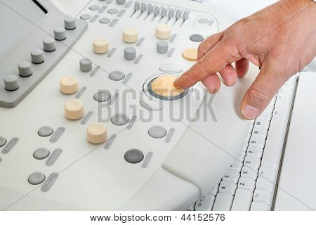 Close up of male hand operating ultrasound machine
