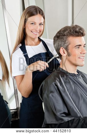 Portrait of female hairdresser cutting client's hair in salon