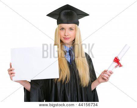 Young Woman In Graduation Gown With Diploma Showing Blank Billbo