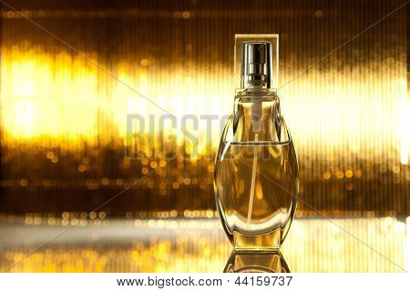 Bottle of perfume on golden background