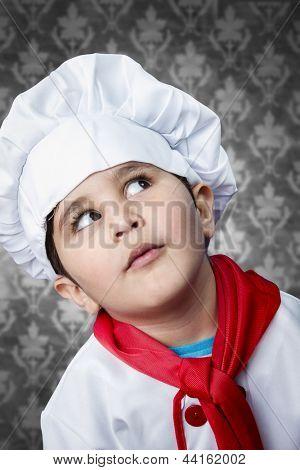 Happy boy cook in uniform over vintage  background funny look