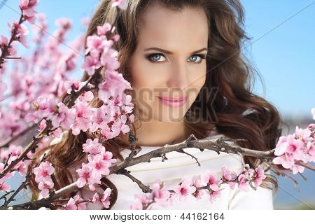 Outdoors Portrait Of Beautiful Smiling Woman Model In Pink Blossoms On Spring Day