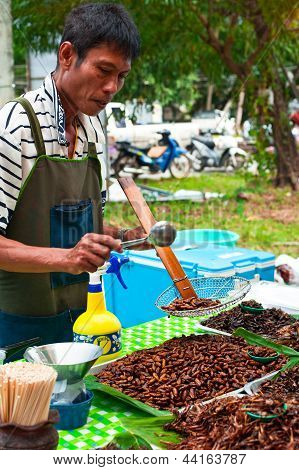 Thai Man Selling Fried Insects At Market