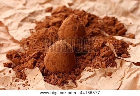 Chocolate truffles and cocoa, on brown background