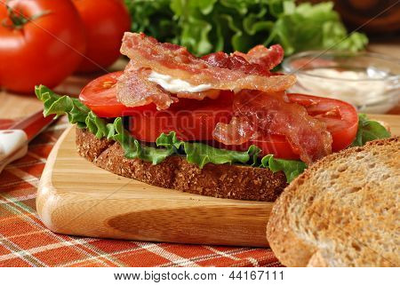 Freshly prepared blt sandwich on wooden cutting board with knife.  Tomatoes, lettuce, and mayo in background and toasted whole grain wheat bread in foreground.  Macro with shallow dof.