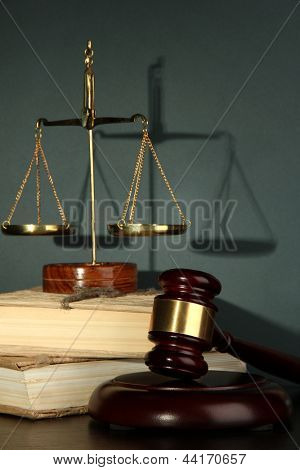 Golden scales of justice, gavel and books on grey background