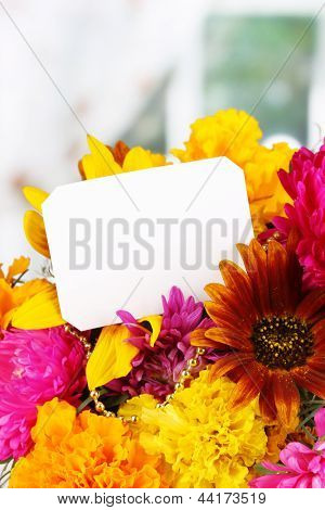 Beautiful bouquet of bright flowers with paper note close-up on wooden table on window background