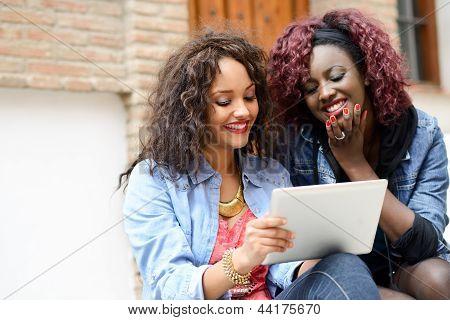 Duas belas garotas com computador Tablet em Backgrund urbano