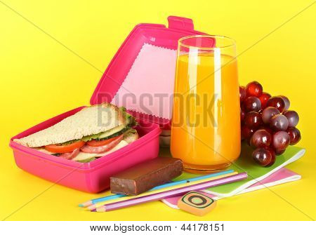 Lunch box with sandwich,grape,juice and stationery on yellow background