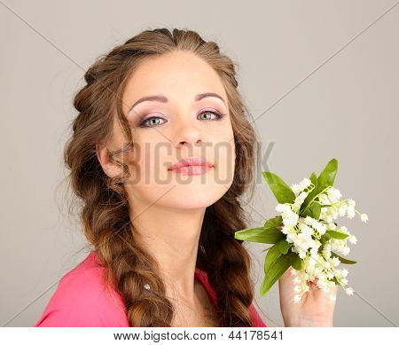 Young woman with beautiful hairstyle and flowers, on grey background