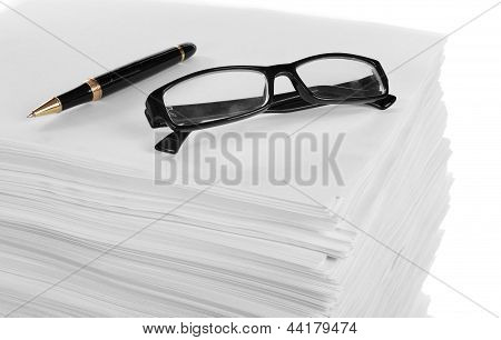 Close Up Of Glasses And Pen On A Stack Of Paper.