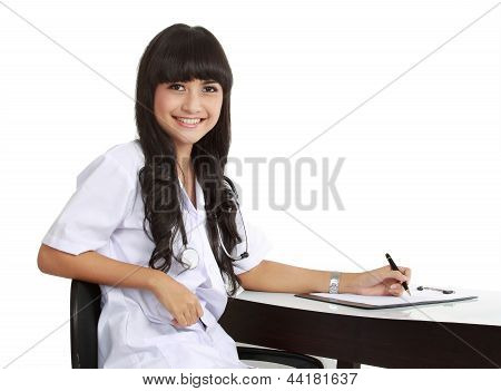 Young Woman Doctor Writing Prescription