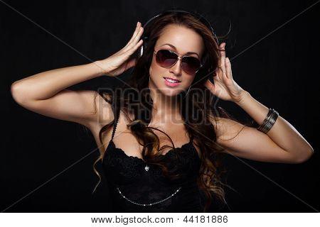 Mujer sexy en gafas de sol escuchando la música con auriculares