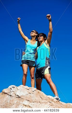 couple trail running on mountain at top celebrating with confident smile and healthy lifestyle