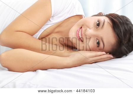 Woman Smiling While Lying Down On Bed