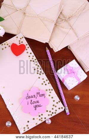 Writing letter of congratulations to mother's Day on wooden table close-up