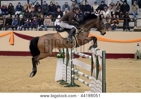 KAPOSVAR, HUNGARY - MARCH 24: Jozsef Pirik jumps with his horse (Starlet) on the Masters Tournament International Jumping Competition, March 24, 2013 in Kaposvar, Hungary