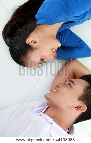 Couple Lying On The Floor, Happy Smile Looking To Each Other