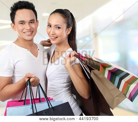 Attractive Happy Couple Carrying Shopping Bag