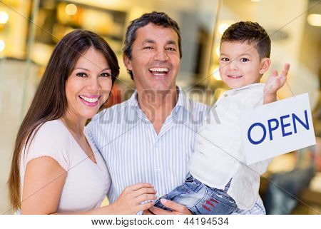 Family at the mall holding an open sign