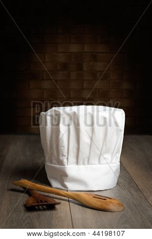 Chef's hat with wooden spoons on abstract wall background
