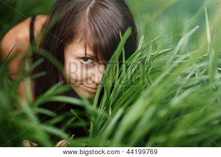 Portrait of beautiful girl hiding in green grass.