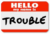 image of annoying  - A namtag sticker with the words Hello My Name is Trouble representing a problem - JPG