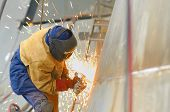 picture of shipyard  - worker grinding metal inside of shipyard - JPG