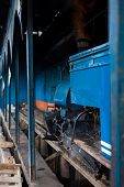 picture of darjeeling  - The front of a toy train engine a local tourist attraction idles in its shed as steam escapes from its smokestack in Darjeeling India - JPG