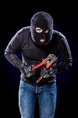 image of wire cutter  - a burglar wearing a balaclava holding huge wire cutters over black background - JPG