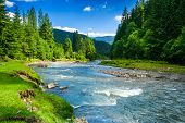 stock photo of mountain-range  - landscape with mountains trees and a river in front - JPG