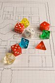 picture of tetrahedron  - Multicolored role play dice sitting on a graph paper hand drawn game map - JPG