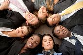 image of ethnic group  - business group with heads together on the floor and their eyes closed in an office - JPG