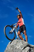 confident mountain bike man celebrating making the top of the peak happy and cheerful