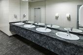 stock photo of public housing  - Row of wash basins with mirrors in public toilet  - JPG