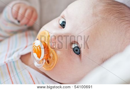 Cute Baby With Pacifier Lying In A Cradle